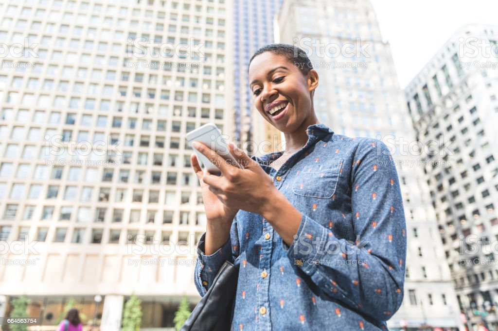 Black woman typing on the phone in the city stock photo