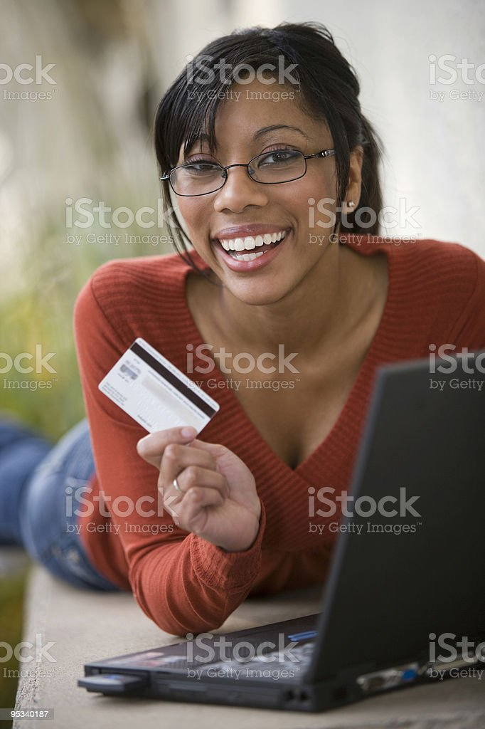Black woman using credit card and laptop outside royalty-free stock photo