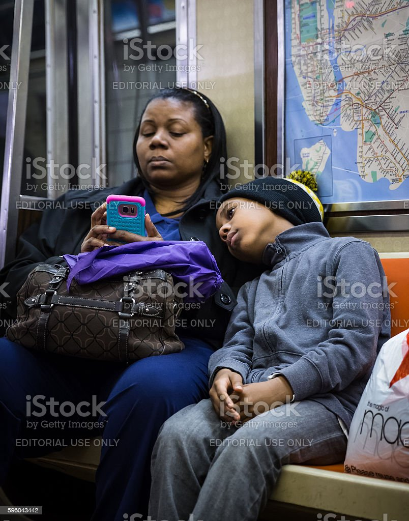 Black woman with a child in New York City subway stock photo