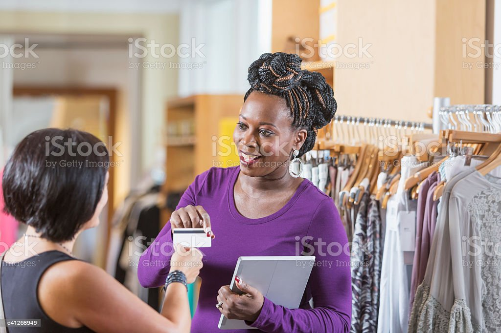 Black woman working in clothing store accepting payment stock photo