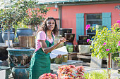Black woman working in garden center taking inventory