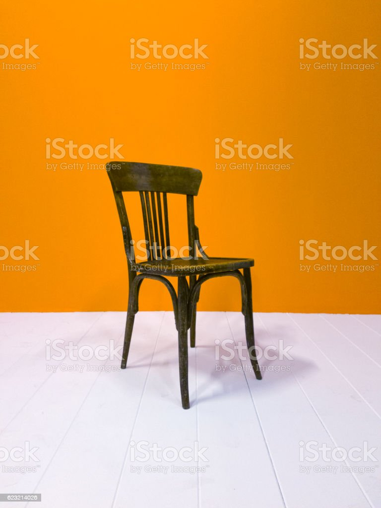 Black wooden chair and orange painted wall stock photo