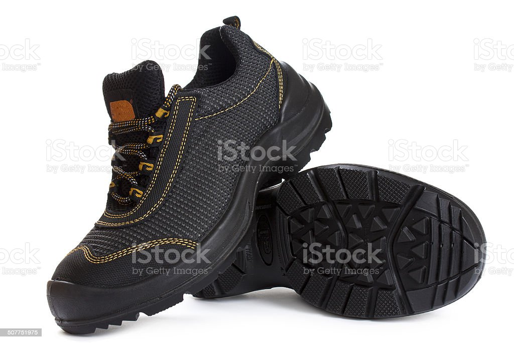 Black working boots with yellow thread on white stock photo