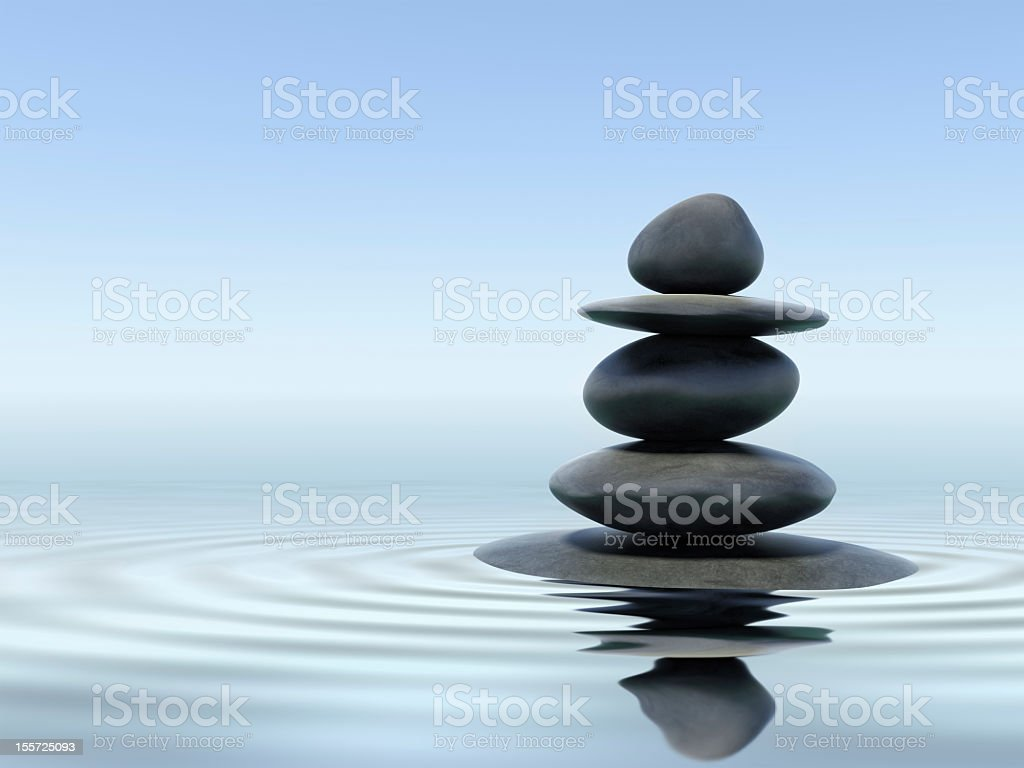 Black zen stones in shallow water stock photo