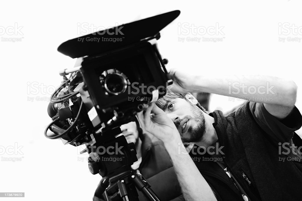 Black-and-white angled young man adjusting a movie camera stock photo