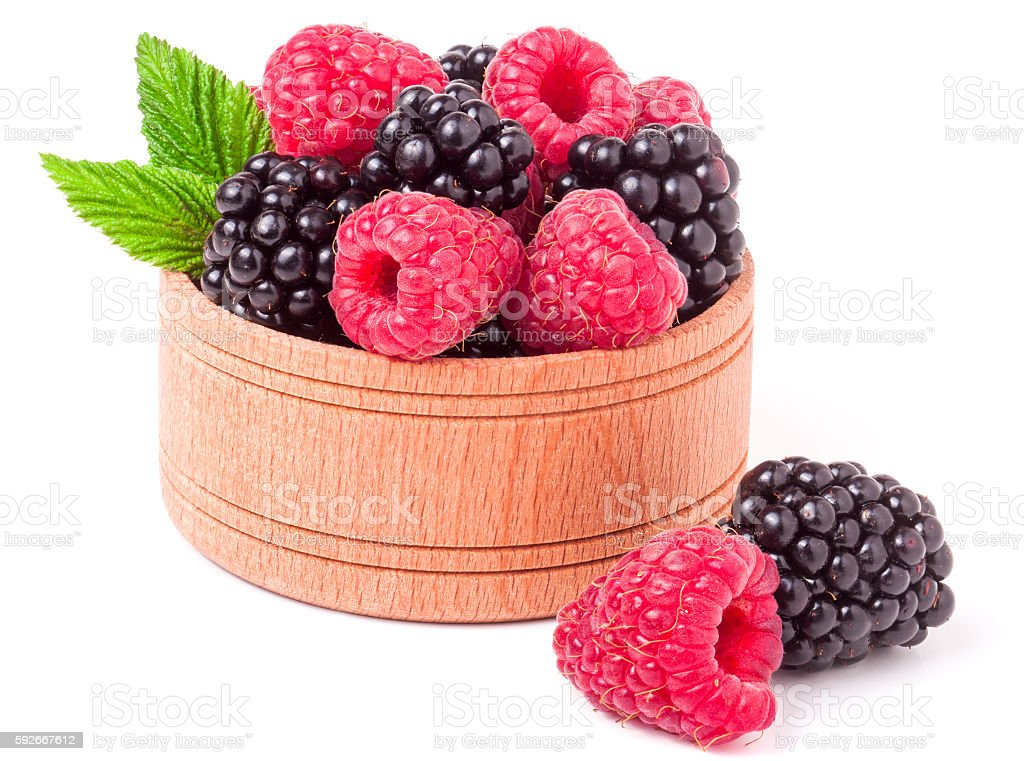 blackberries and raspberries spilled from wooden bowl isolated on white stock photo