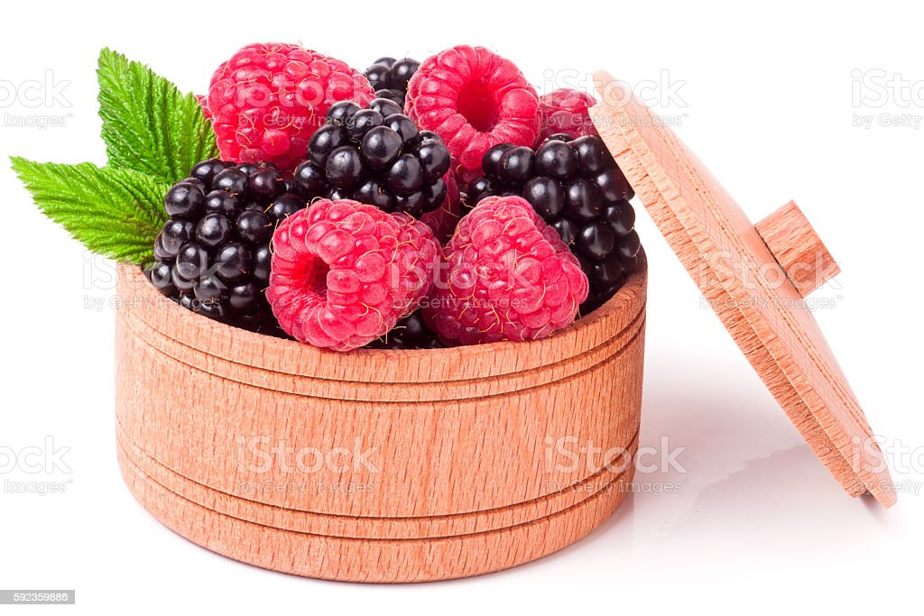 Blackberries and raspberries with leaves in a wooden bowl isolated stock photo