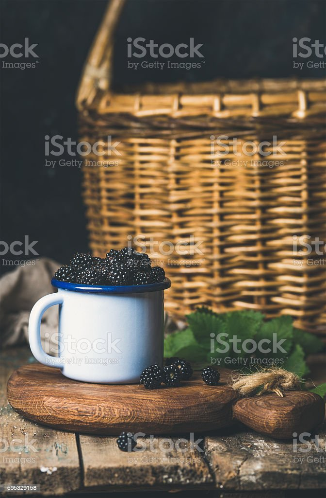 Blackberries in white cup on wooden board over rustic table stock photo