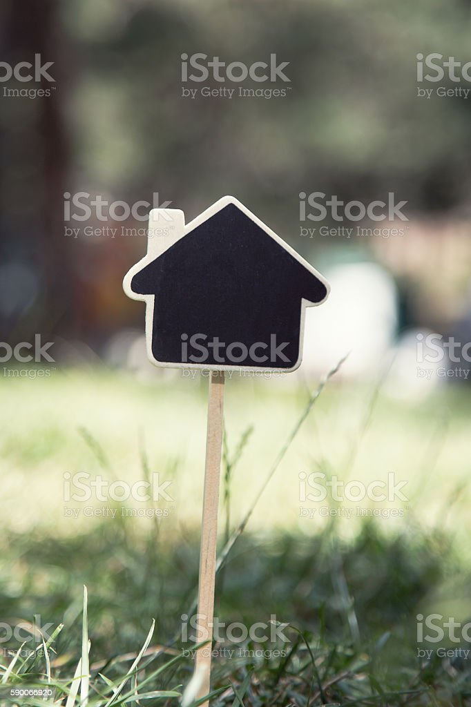 blackboard in the shape of house on nature background stock photo