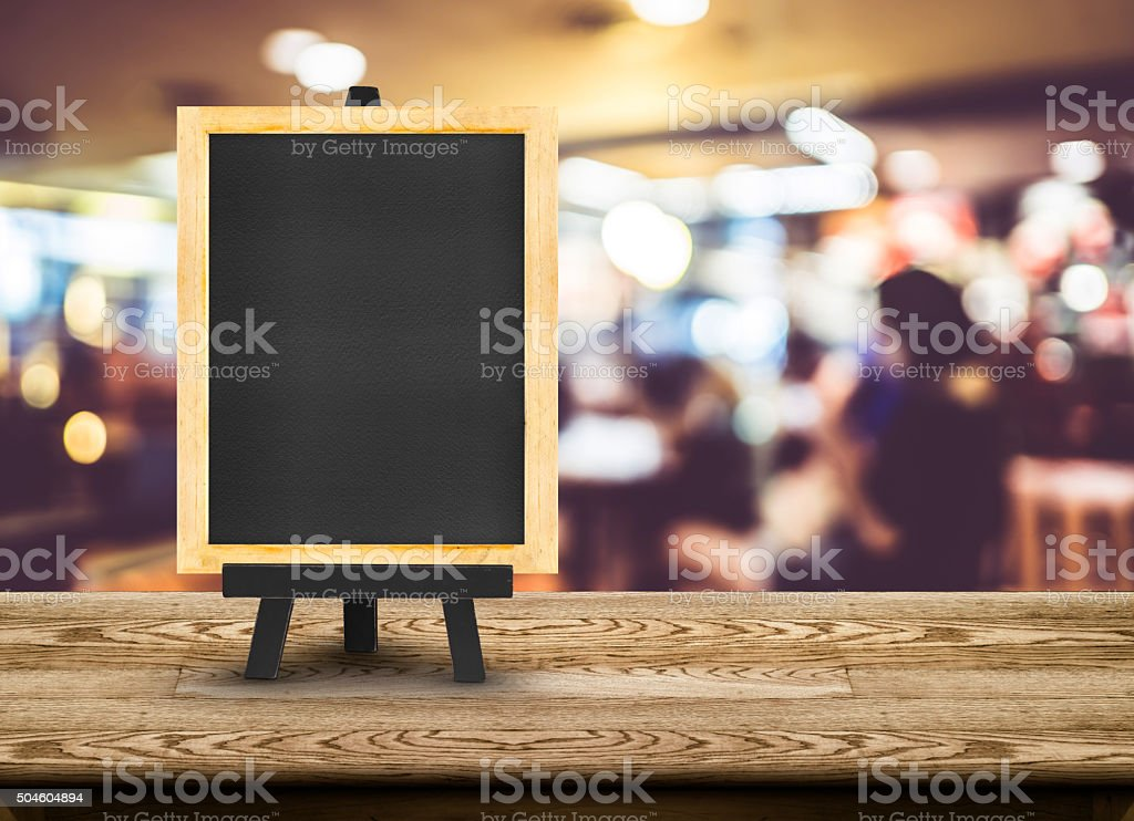 Blackboard menu with easel on wooden table with blur restaurant stock photo
