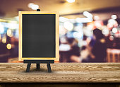 Blackboard menu with easel on wooden table with blur restaurant