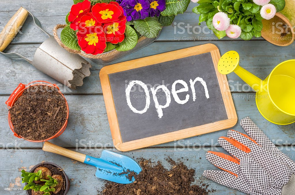 Blackboard on a plant table with garden tools - Open stock photo