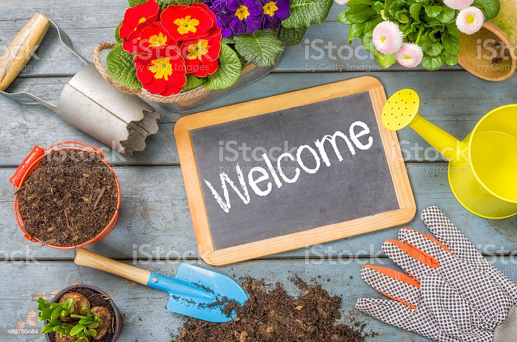 Blackboard on a plant table with garden tools - Welcome stock photo