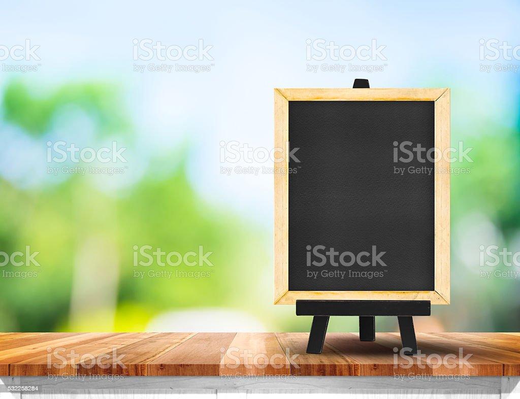 blackboard on wood table top with sun and blur tree stock photo