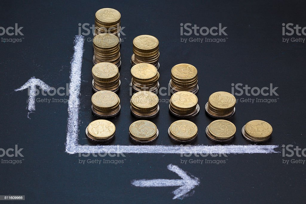Blackboard showing a decrease with coins stock photo