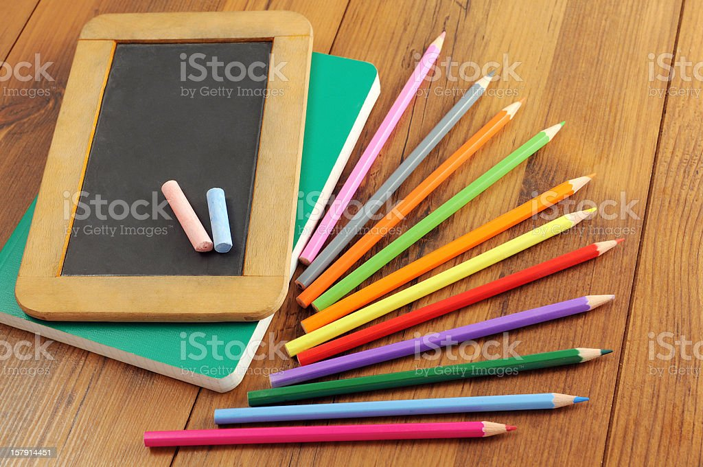 blackboard with copyspace laying on school work books and crayons. stock photo
