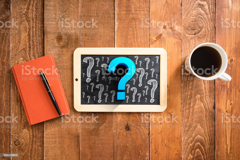 Blackboard with question marks on wooden plank background with coffee stock photo