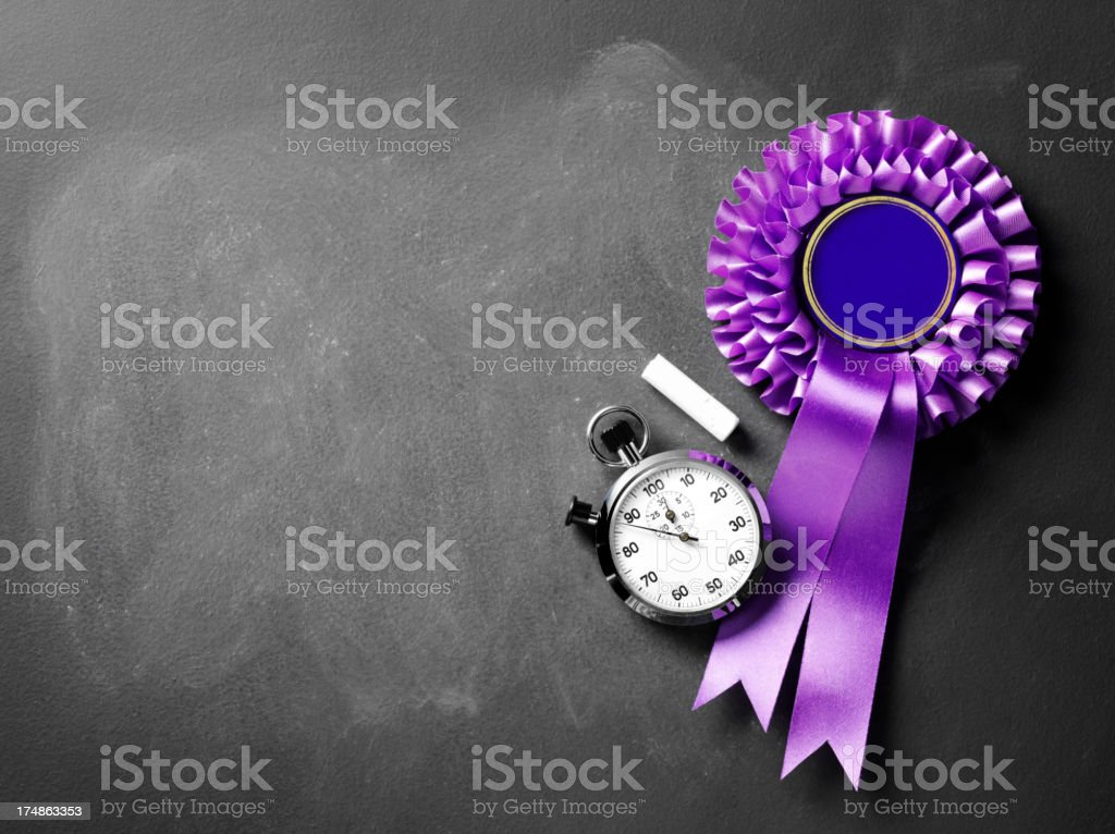 Blackboard with Stopwatch and Purple Rosette royalty-free stock photo