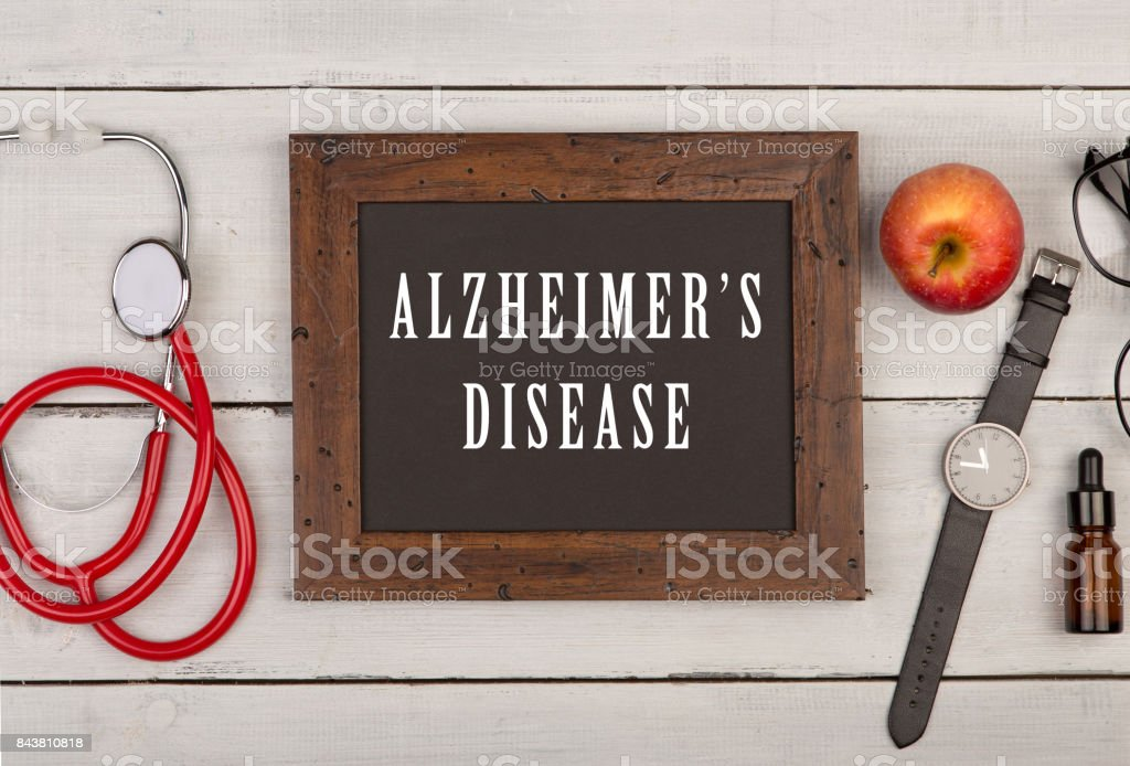 blackboard with text 'Alzheimer's disease', watch and stethoscope stock photo