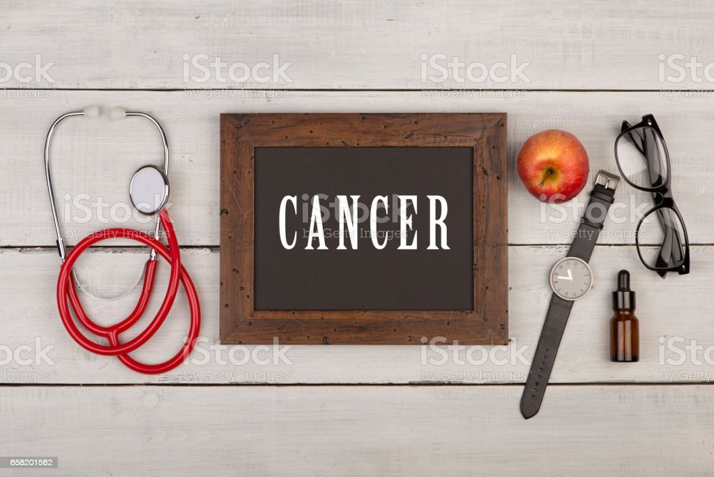 Blackboard with text 'Cancer', watch, eyeglasses and stethoscope stock photo