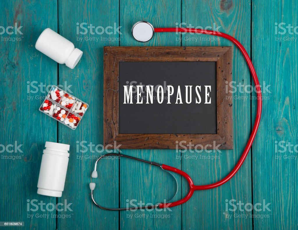 Blackboard with text 'Menopause', stethoscope, pills on blue wooden background stock photo