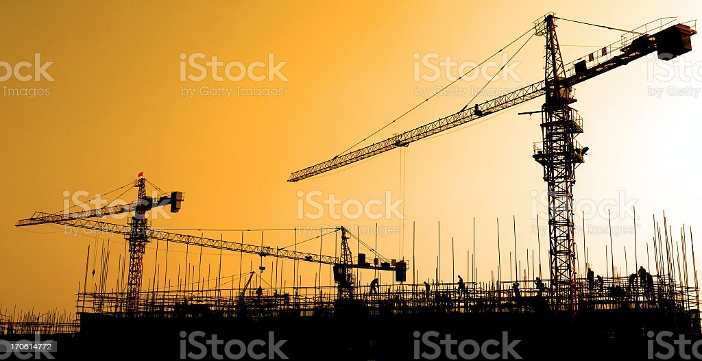 Blacked out cranes against a bright, orange sky royalty-free stock photo