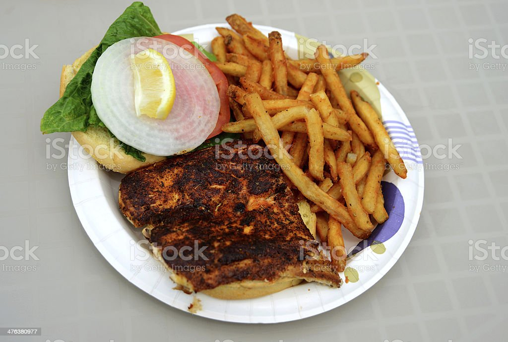 blackened fish sandwich and french fries royalty-free stock photo