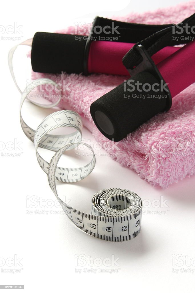 Black-pink dumbbell with handle and measuring tape on towel royalty-free stock photo
