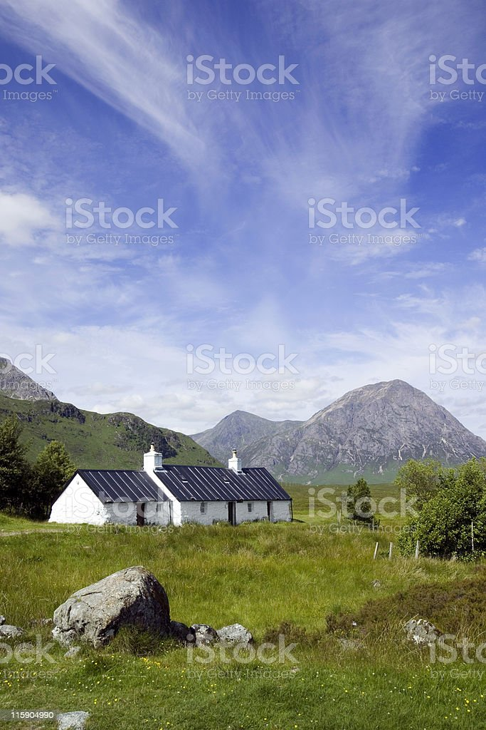 Blackrock cottage with cloud formations over mountains royalty-free stock photo