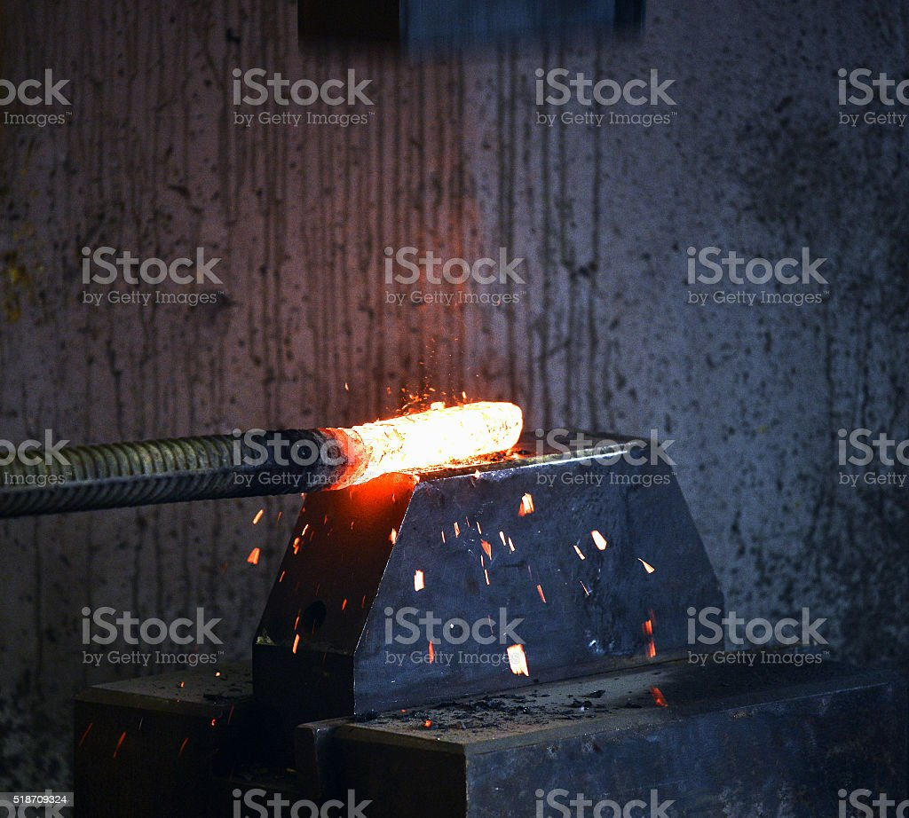 Blacksmith forges a red-hot iron stock photo