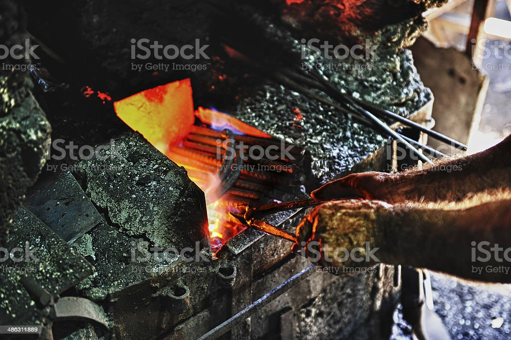 Blacksmith forging metal in fire stock photo