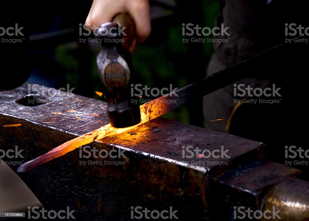 Blacksmith hammering a hot metal rod stock photo