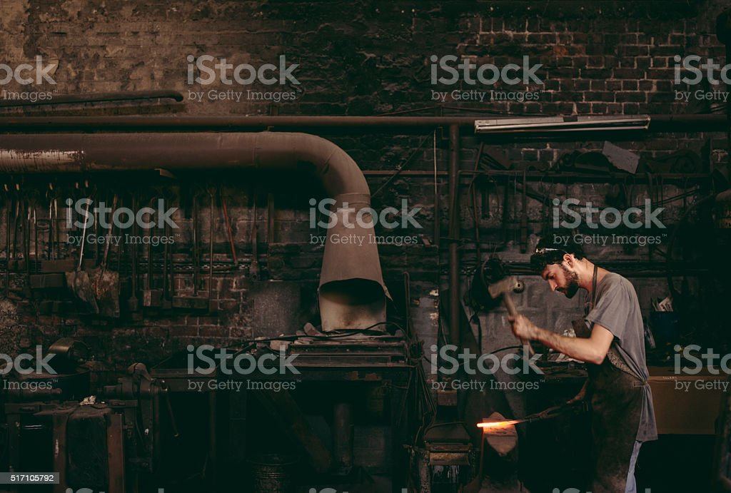Blacksmith hammering glowing iron on anvil in workshop stock photo
