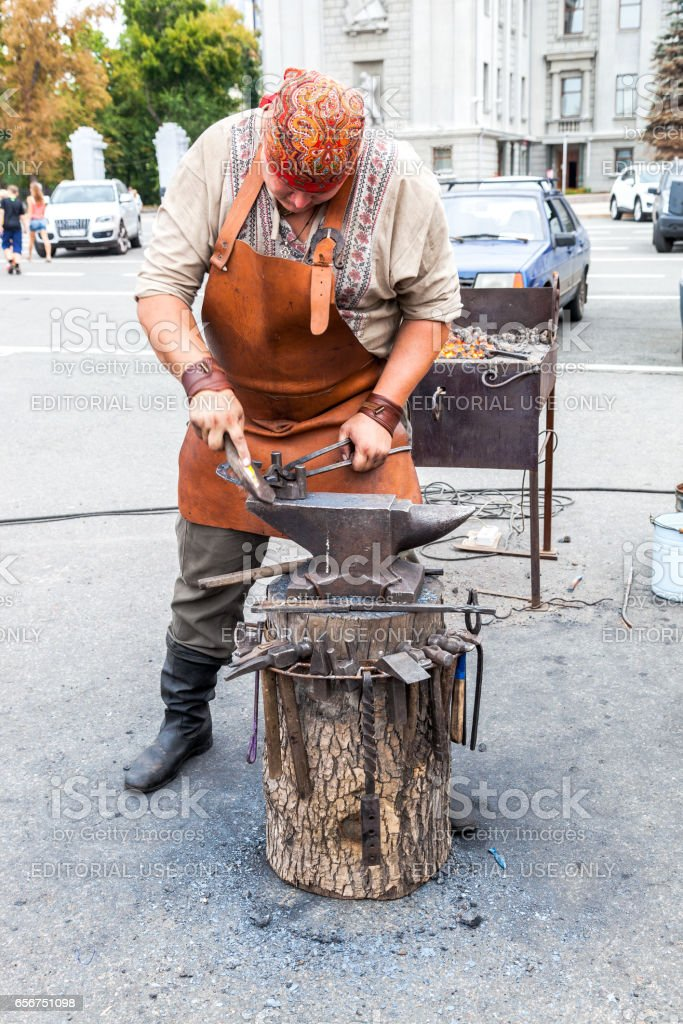 Blacksmith handles the horseshoe on the anvil at the outdoors stock photo
