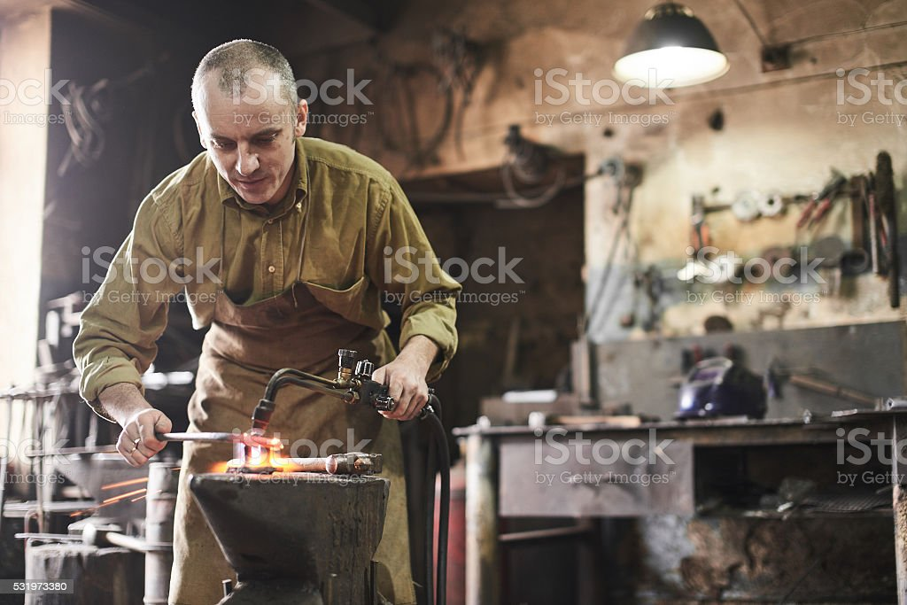 Blacksmith heats metal with a gas burner stock photo