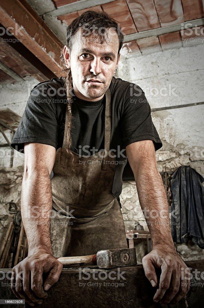 A blacksmith leaning on his anvil stock photo