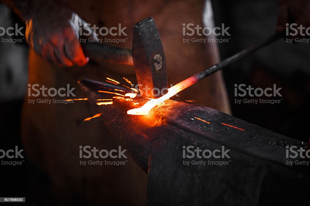 Blacksmith manually forging the molten metal stock photo