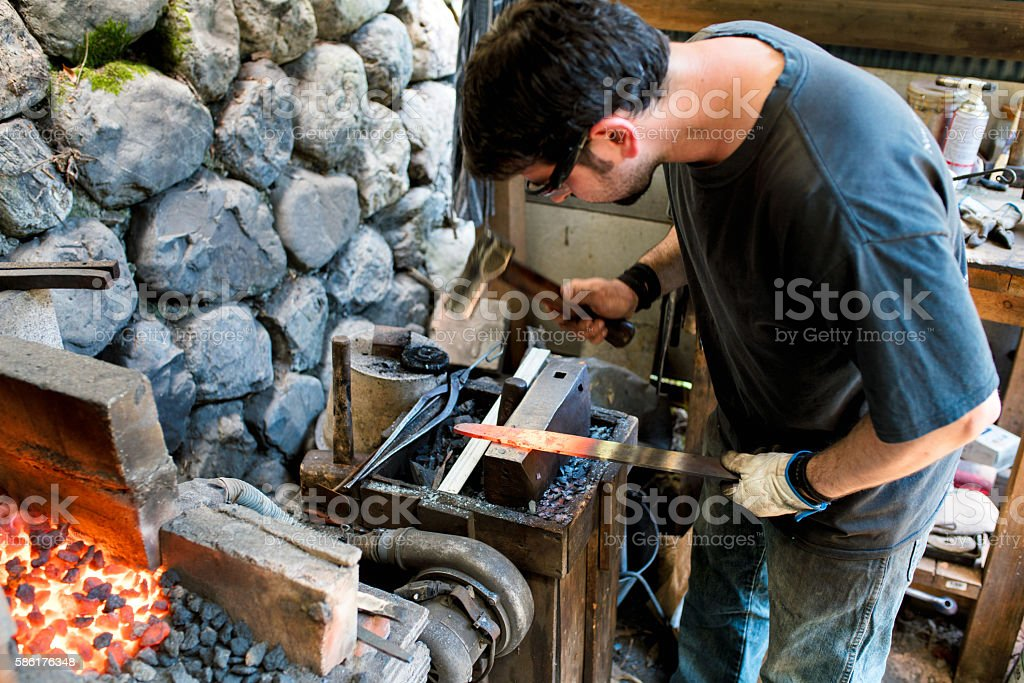 Blacksmith shaping a traditional Japanese cooking knife stock photo
