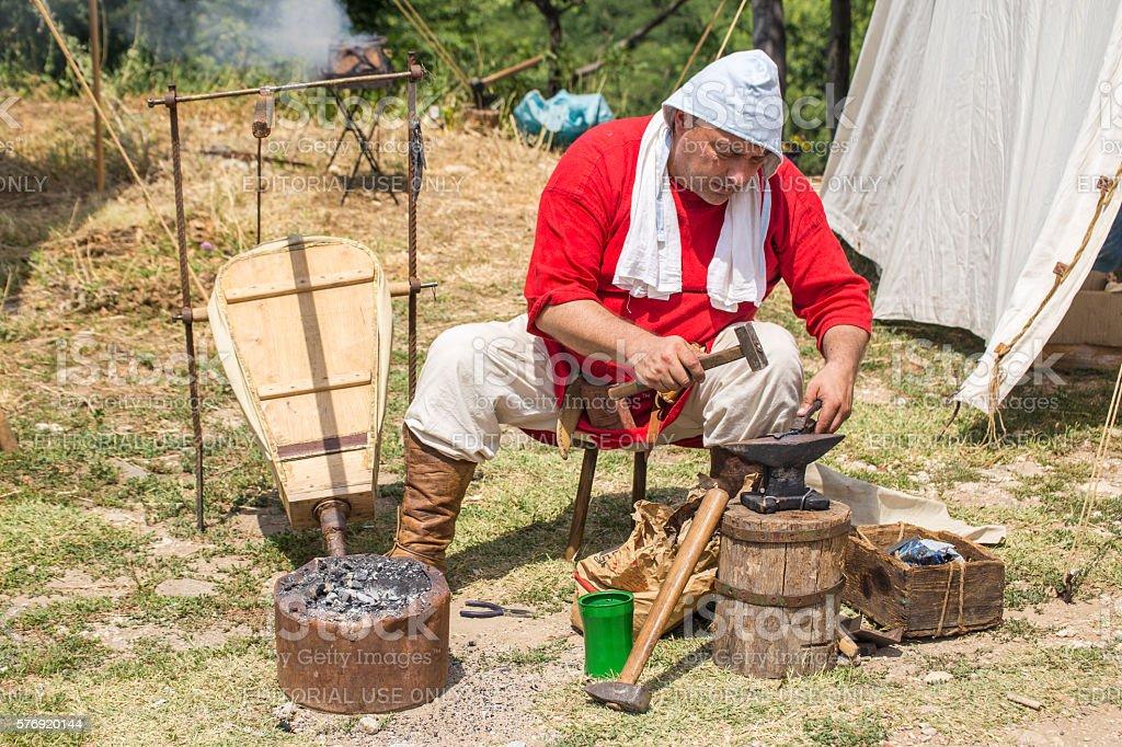 Blacksmith working outdoors stock photo