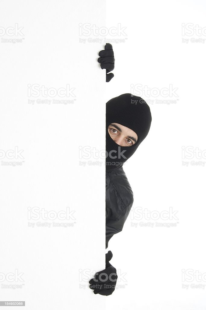 Black-wearing thief spying out the white wall/background stock photo