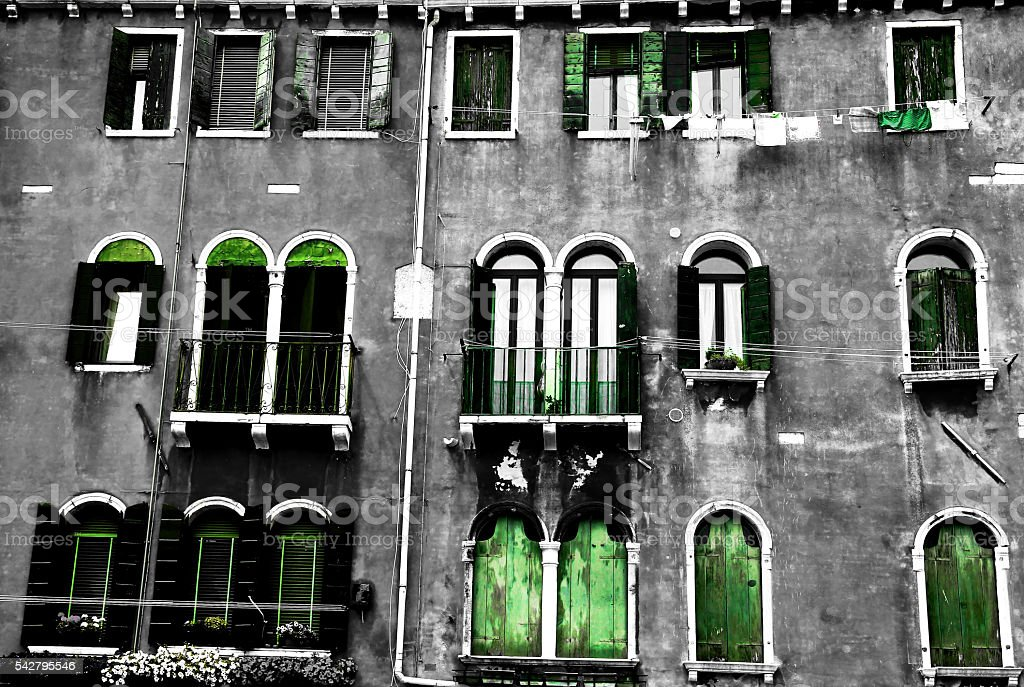 Black-white house facade with green shutters stock photo