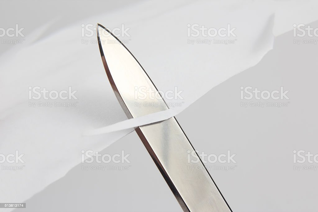 blade of a sharp knife cut across the white paper stock photo