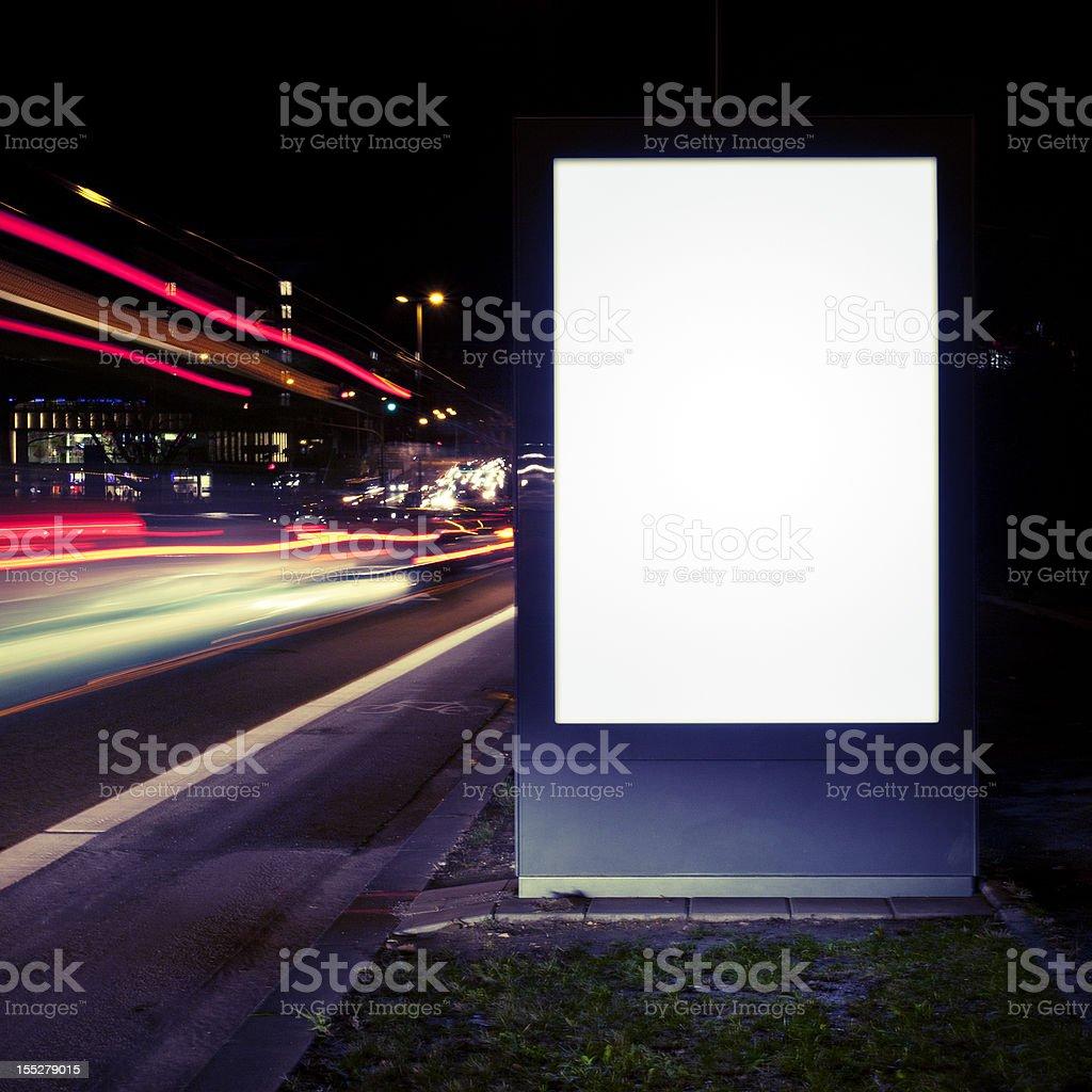 Blank advertising billboard on city street at night stock photo