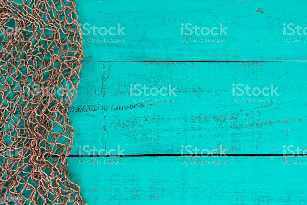 Blank antique teal blue wooden sign with fish net border stock photo