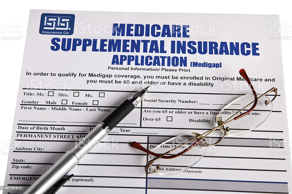 Blank application for Medicare Supplemental Insurance, with glasses and pen royalty-free stock photo