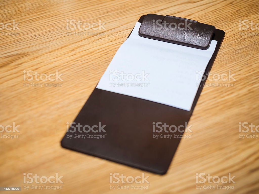 Blank Bill Receipt Restaurant Clip in pad on Table stock photo