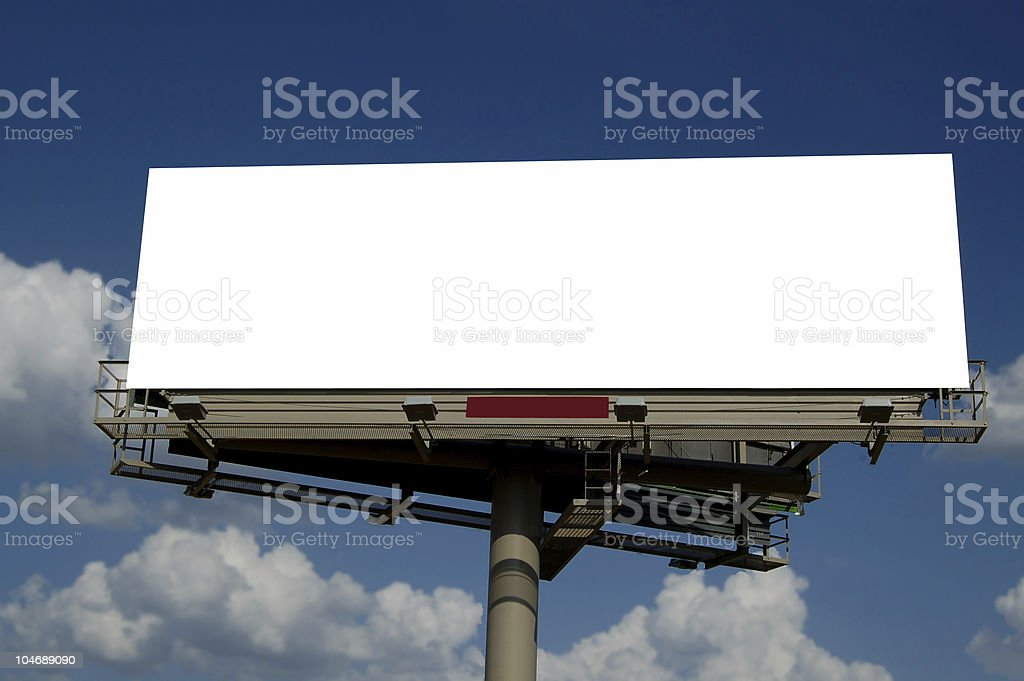 Blank billboard against a bright blue sky with clouds royalty-free stock photo