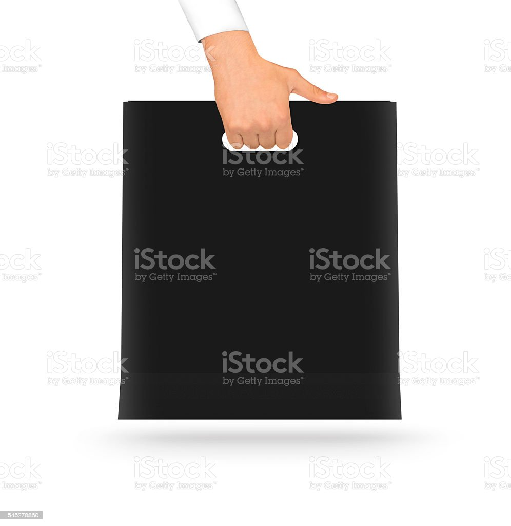 Blank black paper bag mock up holding in hand. Empty stock photo