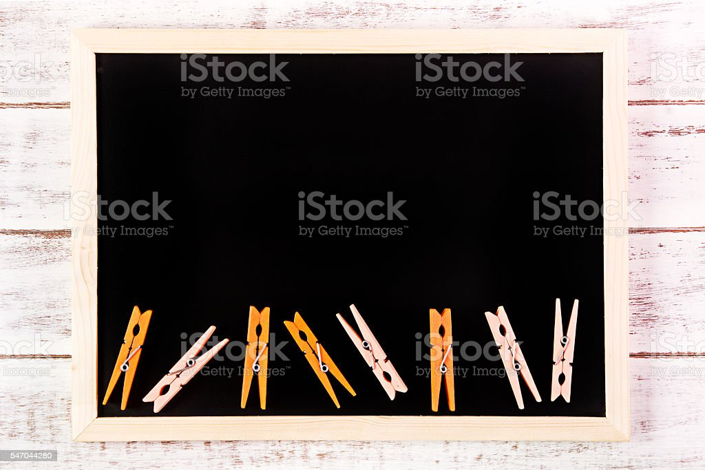 Blank blackboard and Orange clothes peg stock photo