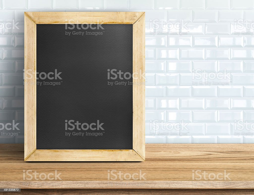 Blank blackboard on tropical wooden table at white tile wall stock photo